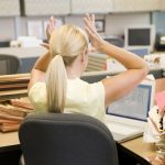 woman sitting a file filled desk with her hands above her head feeling stressed