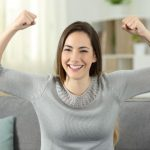 Young woman smiling and holding up both arms in success
