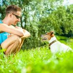 Picture of young man kneeling down in front of a Jack Russell terrier dog, outdoors on grass.