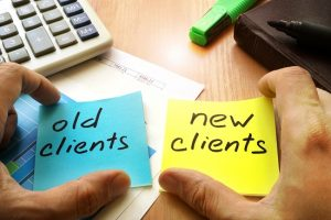 Hands holding two notes on a desk, one says old clients, the other says new clients.