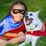picture of small girl dressed in a cape, sitting on a lawn with her arm around a caped dog