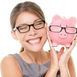 photo of a smiling woman holding a pink piggy bank. Both are wearing glasses
