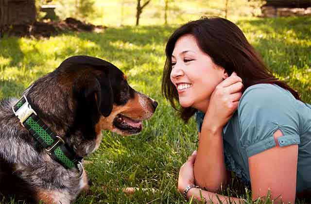 Picture of woman on her stomach face to face with dog on grass